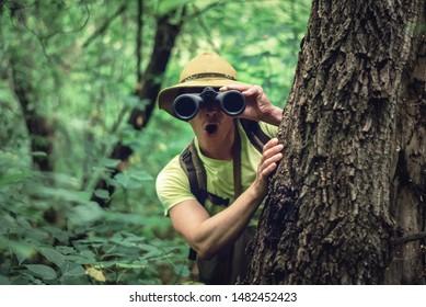 Amazed traveler in hat is looking through binoculars over green forest background.