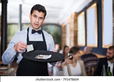 Amazed waiter holds money for order in a restaurant