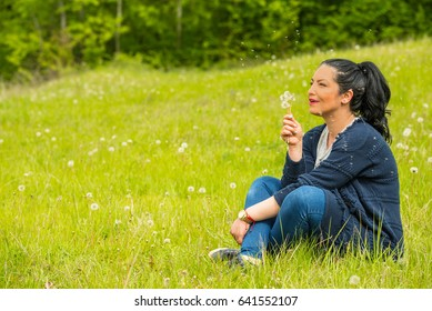 Amazed woman blowing seeds dandelions and wishing in nature