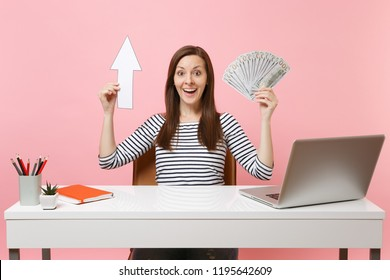 Amazed woman holding up arrow, bundle lots of dollars cash money sit work at white desk with contemporary pc laptop isolated on pastel pink background. Achievement business career concept. Copy space