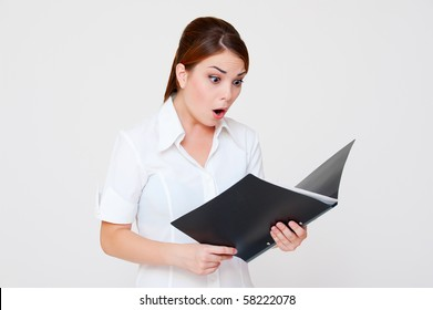 amazed woman looking in her report over grey background