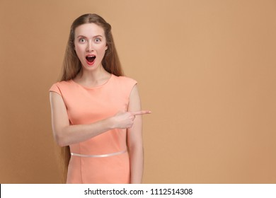 Amazed woman pointing side and looking at camera. portrait of emotional cute, beautiful woman with makeup and long hair in pink dress. indoor, studio shot isolated on light brown or beige background.