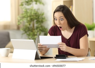 Amazed woman reading good news in a letter sitting in a desk at home