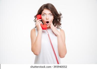 Amazed woman talking on the phone tube isolated on a white background