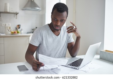 Amazed young african american male, sitting at kitchen table, holding cup of coffee in hand, looking at bill with concentrated puzzled expression, surprised by high taxes. Financial problems concept