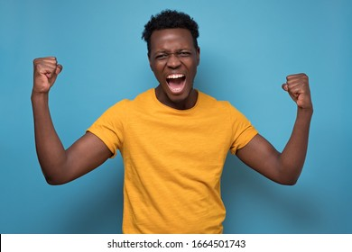 Amazed young African American man in yellow clothes holding fists in surprised gesture, celebrating his success. Studio shot