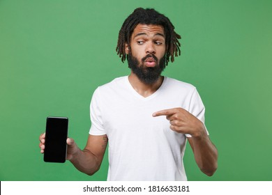 Amazed young african american man 20s in white t-shirt pointing index finger on mobile cell phone with blank black empty screen with mock up copy space isolated on green background studio portrait