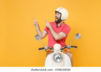Amazed young bearded man guy in casual summer clothes helmet driving moped isolated on yellow background. Driving motorbike transportation concept. Mock up copy space. Pointing index fingers aside up
