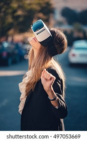Amazed young beautiful girl wearing virtual reality 3D video glasses VR headset dressed in a office outfit impressed by augmented reality on the street and beautiful autumn sun light colors