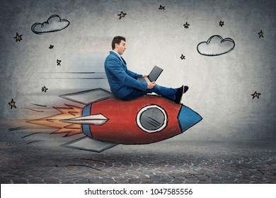Amazed young businessman flying on a fast rocket looking at his laptop monitor. Global network speed concept. Business success and high targets.