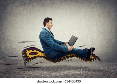 Amazed young businessman looking at a laptop monitor while riding a magic flying carpet.  Global network speed concept.