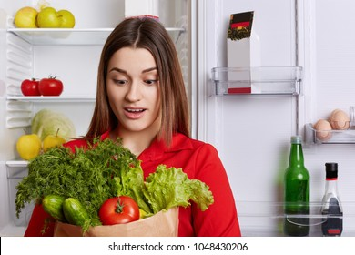 Amazed young female with surprised expression looks at vegetables, forgets to buy something in grocer`s shop, stands in kitchen near refrigerator. People, healthy nutrition and dieting concept.