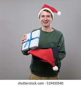 Amazed young man in christmas red hat open present on grey background