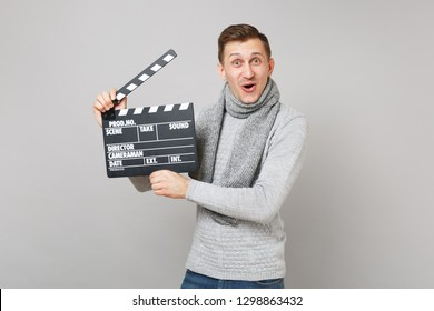 Amazed young man in gray sweater, scarf holding classic black film making clapperboard isolated on grey background. Healthy lifestyle, people sincere emotions, cold season concept. Mock up copy space
