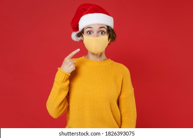 Amazed young Santa woman in Christmas hat pointing index finger on face mask safe from coronavirus virus covid-19 isolated on red background studio. Happy New Year celebration merry holiday concept