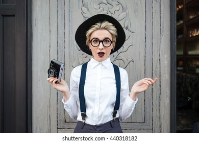 Amazed young woman photographer in black hat standing and holding photo camera