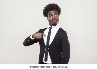 Amazement aloof afro man looking at camera and pointing finger himself. Studio shot, gray background