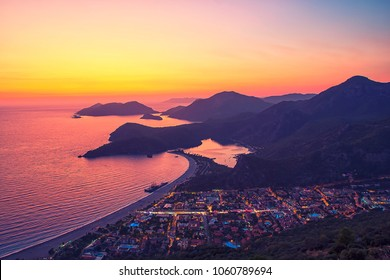 Amazing aerial view of beautiful sunset Blue Lagoon in Oludeniz, Turkey. Summer landscape with beach and mountains, green forest, azure water, sandy beach and blue sky in bright sunny day best tourist