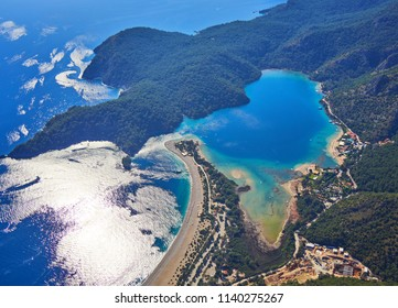 Amazing aerial view of Blue Lagoon in Oludeniz, Turkey. Summer landscape with sea spit, green trees, azure water, sandy beach in bright sunny day. Travel background. Top view of national park.