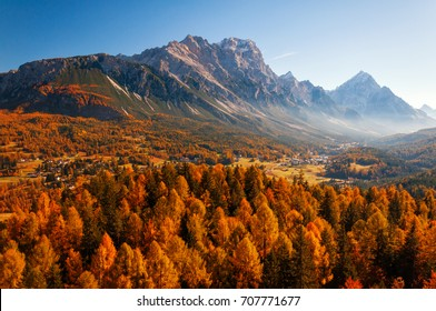 Amazing aerial view of the Dolomite Alps at sunny autumn day with yellow larches below and valley covered by fog and high mountain peaks behind. Cortina d'Ampezzo, Veneto, Italy.