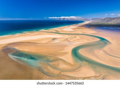 Amazing aerial view of icelandic Raudasandur beach with azure water streams and yellow sand