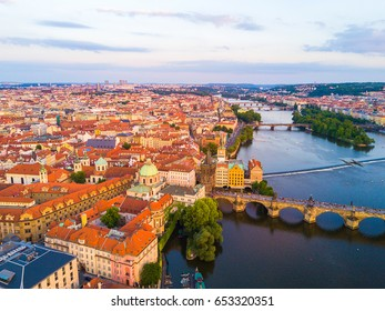 Amazing aerial view of the Prague city Charles bridge from above. Beautiful city landscape view during sunset over the river Vltava.