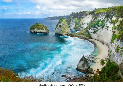 Amazing aerial view of a secret beach located in Nusa Penida, southeast of Bali Island, Indonesia. Wonderful seashore cliffs meet the great blue and turquoise ocean in a sunny blue sky.