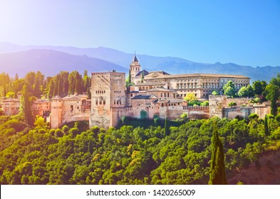 Amazing Alhambra palace complex taken in the morning in sunrise light. Beautiful piece of Moorish architecture, surrounded by green trees, is located in Granada, Spain.