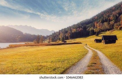 Amazing Alpine valley wth ground road and wooden huts under warm sunlit. Fairy landscape with perfest sky over the mountains in European Alps. Wonderful nature Background. Creative toned image.