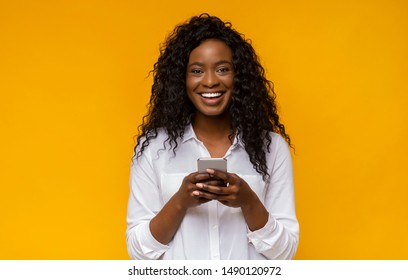 Amazing application. Super happy black woman using smartphone on yellow background