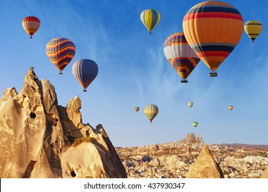 Amazing attraction and adventure in Kapadokya, hot air balloons flying above unusual rocky landscape in Cappadocia, Turkey