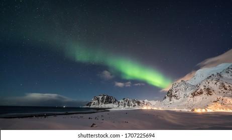 Amazing Aurora Borealis dancing over famous Uttakleiv Beach during a cold arctic night on Lofoten Islands archipelago in winter, Norway, Scandinavia