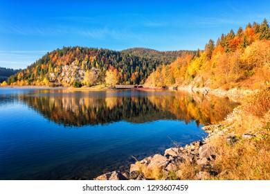 Amazing autumn landscape with alpine lake, golden colored wooded mountain and blue sky, outdoor travel background, National park Slovak paradise (Narodny park Slovensky Raj), Slovakia (Slovensko)