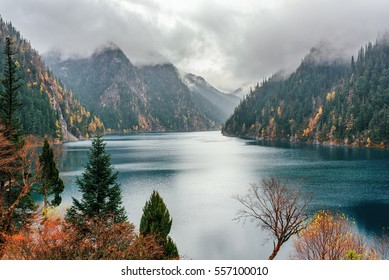 Amazing autumn landscape at Jiuzhaigou nature reserve (Jiuzhai Valley National Park) of Sichuan province, China. Scenic view of the Long Lake among fall wooded mountains in fog.