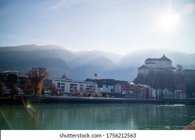 Amazing autumn landscape with Kufstein Fortress and traditional houses on a boardwalk of smooth Inn river on a forefront on a background of clear sunny sky, Kufstein Austria.