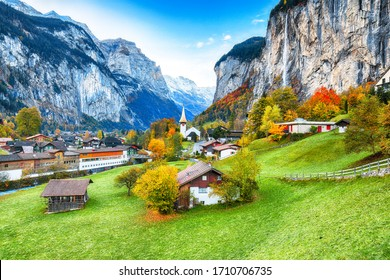 Amazing autumn landscape of touristic alpine village Lauterbrunnen with famous church and Staubbach waterfall. Location: Lauterbrunnen village, Berner Oberland, Switzerland, Europe.