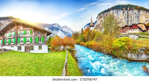 Amazing autumn landscape of touristic alpine village Lauterbrunnen with famous church and Staubbach waterfall. Location: Lauterbrunnen village, Berner Oberland, Switzerland, Europe.