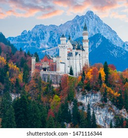 Amazing autumn view on Neuschwanstein Castle with colorful trees and the Alps on background, Bavaria, Germany. Beautiful autumn colorful scenery.