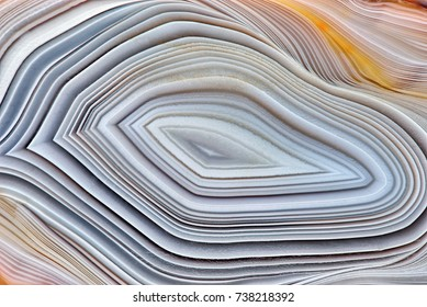 Amazing Banded Agate Crystal cross section as a background. Natural light translucent agate crystal surface, Gray abstract expressive structure slice mineral stone macro closeup