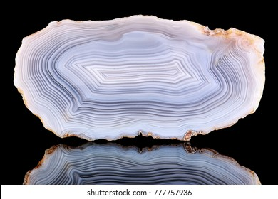 Amazing Banded Agate Crystal cross section cut isolated on black background with reflection. Natural light translucent agate crystal surface, Gray abstract structure slice mineral stone macro closeup