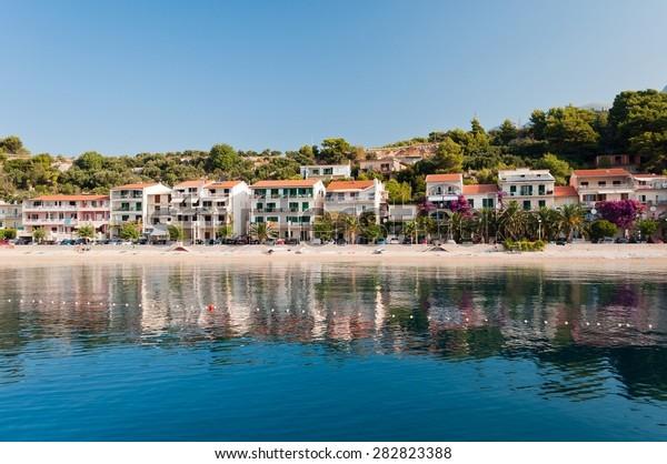 Amazing beach with apartments and palm trees in Makarska Riviera in Podgora-Caklje, Croatia