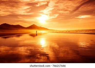 Amazing beach sunset with endless horizon and lonely figures in idyllic warm colors