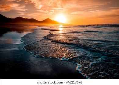 Amazing beach sunset with endless horizon and lonely figures in the distance, and incredible foamy waves. Volcanic hills in the background in idyllic warm colors.