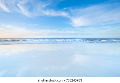 Amazing beach sunset with endless horizon and smooth cloud in pale blue color tone