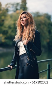 Amazing beautiful blonde young party girl next season in autumn feelings punky mood made itself felt in motocross leathers and onslaught of the ski pant on autumn background colors beautiful sun light