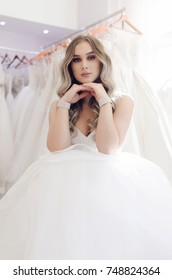 Amazing beautiful bride woman portrait in wedding clothes dresses salon with hands on her chin