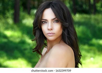 Amazing beautiful brunette woman face. Close up portrait on nature background