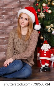 Amazing beautiful face lady girl with perfect skin and blond hairs posing for christmas holidays close to new year green pine tree and presents in studio.