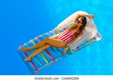 amazing beautiful girl in bikini on an  air mattress swims in the pool of a luxury hotel, summer vacation.