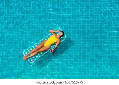 incrível menina bonita em um biquíni amarelo colchão de ar nada na piscina de um hotel de luxo, férias de verão, felicidade, viagens, alegria sorriso, ouvindo música, coquetel, vista superior